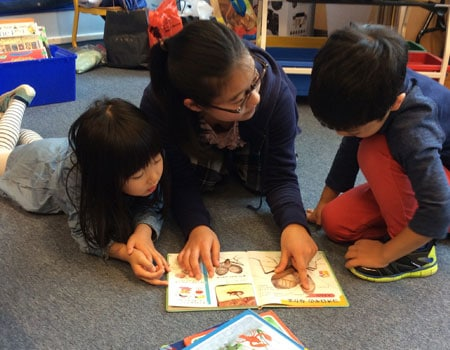 Students reading a book in their mother tongue